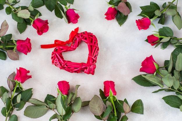 Róże są ułożone w okrąg, a na środku czerwone wiklinowe serce