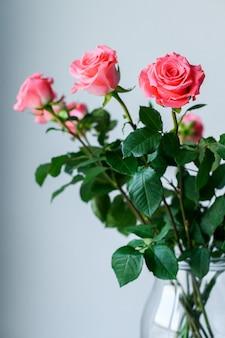 Róże w przezroczystym wazonie na szarym tle z miejscem na tekst.