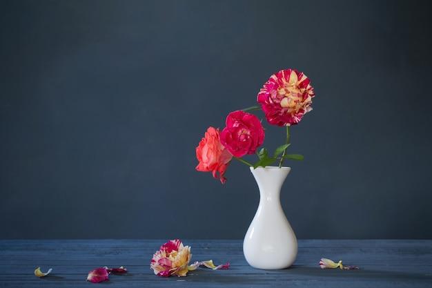 Róże w wazonie na ciemnym niebieskim tle