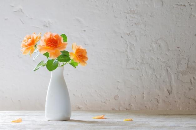 Róże w wazonie na tle białej ściany