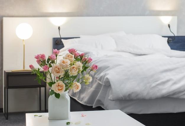 Róże w wazonie z łóżkiem w nowoczesnej sypialni