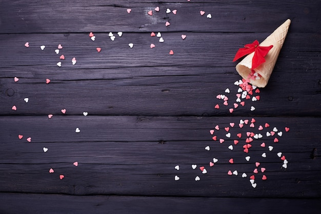 Rożek waflowy i wiele małych serc na czarnym tle. tło romantycznej miłości na walentynki