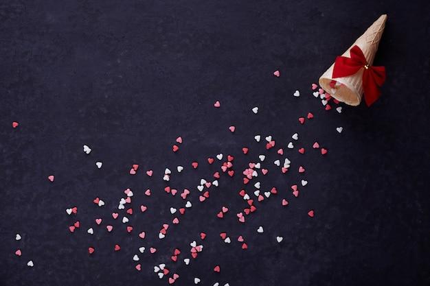 Rożek waflowy i wiele małych serc na czarnym tle. tło romantycznej miłości