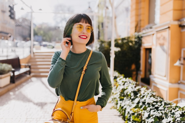Roześmiana atrakcyjna dziewczyna w modnym wiosennym stroju chłodzenie na świeżym powietrzu. zdjęcie szczęśliwej białej kobiety nosi okulary przeciwsłoneczne i żółtą torebkę.