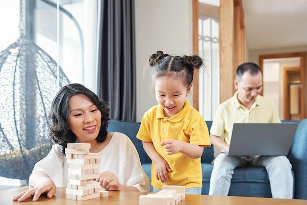 Roześmiana azjatka i jej córeczka, spędzając czas w domu, robią wieże z drewnianych cegieł z powodu blokady