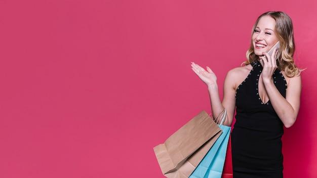 Roześmiana blond kobieta mówi na telefonie z torbami