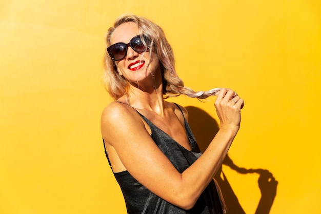 Roześmiana blondynka z długimi włosami w okularach przeciwsłonecznych na żółto