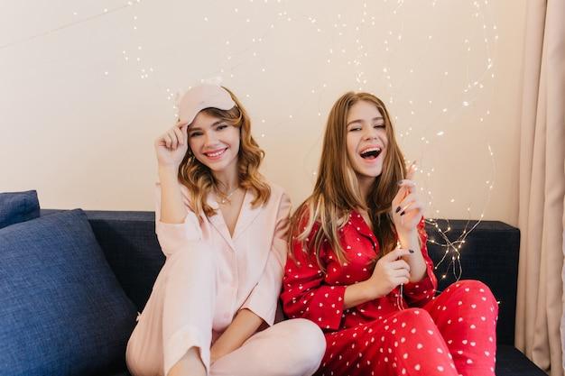 Roześmiana brunetka dziewczyna bawić się żarówkami. wewnątrz zdjęcie dwóch pań w stylowych piżamach siedzących na niebieskiej kanapie.