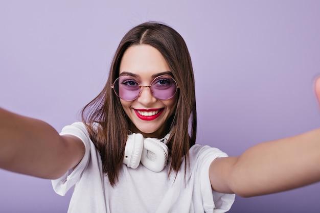 Roześmiana brunetka dziewczyna z białymi słuchawkami robi sobie zdjęcie. kryty strzał czarującej brunetki kobiety w okularach przeciwsłonecznych, dzięki czemu selfie.