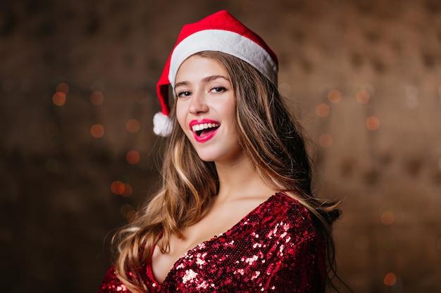 Roześmiana brunetka kobieta w czapce świętego mikołaja czeka na przyjęcie noworoczne