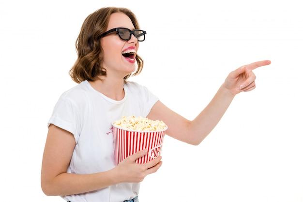 Roześmiana caucasian kobieta trzyma kukurydzanego pop ogląda film.