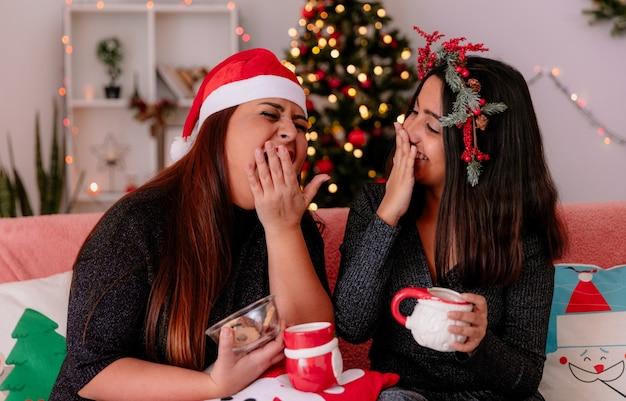 Roześmiana córka i matka obejmujące usta ręką siedzącą na kanapie, ciesząc się bożonarodzeniowym w domu
