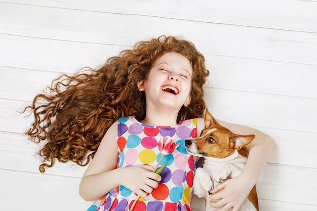 Roześmiana dziewczyna obejmuje psa kłaść na ciepłej drewnianej podłoga.