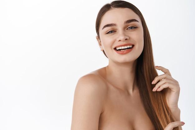 Roześmiana dziewczyna szczotkująca kosmyki włosów ręką i uśmiechnięta z przodu