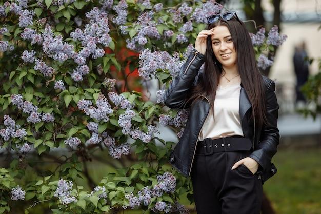 Roześmiana i uśmiechnięta piękna szczęśliwa artystyczna młoda modelka z długimi włosami w letnim bzu