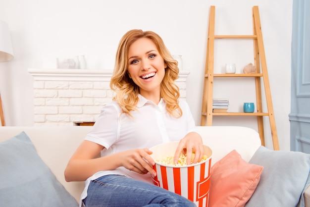 Roześmiana kobieta jedząca popcorn i oglądająca ciekawą komedię