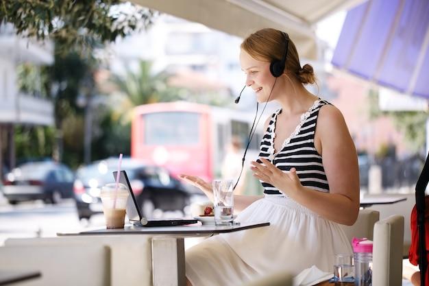Roześmiana kobieta jest ubranym słuchawki w plenerowej kawiarni