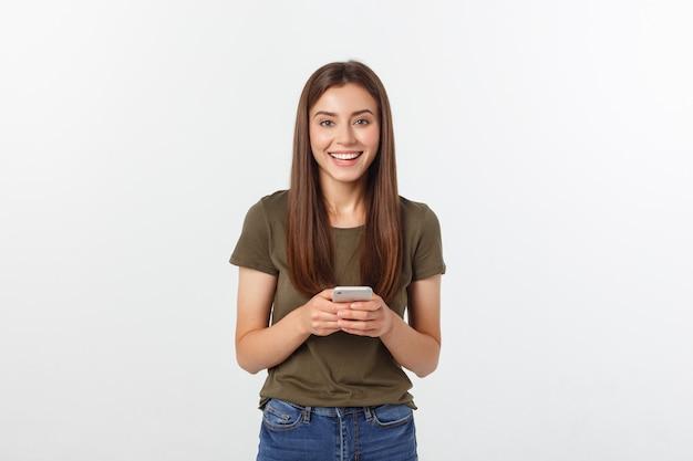 Roześmiana kobieta opowiada i texting na telefonie odizolowywającym na bielu.