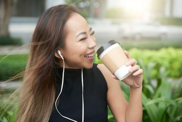 Roześmiana kobieta pije kawę