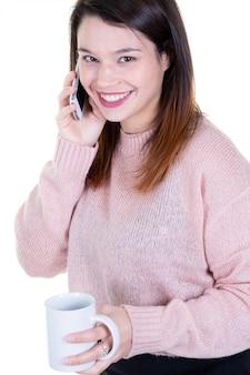 Roześmiana kobieta trzyma mądrze telefon jej ucho i kubek filiżanka herbaty w ręce