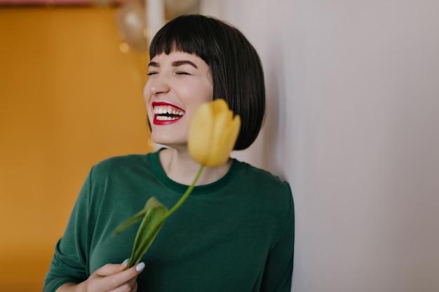 Roześmiana kobieta trzyma żółtego tulipana z krótkimi prostymi włosami. portret przyjemnej białej dziewczyny w zielonym stroju zabawy w wiosenny dzień.