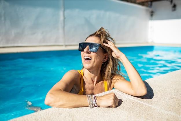 Roześmiana kobieta w basenie. opala się w basenie. ma na sobie żółte stroje kąpielowe i okulary przeciwsłoneczne