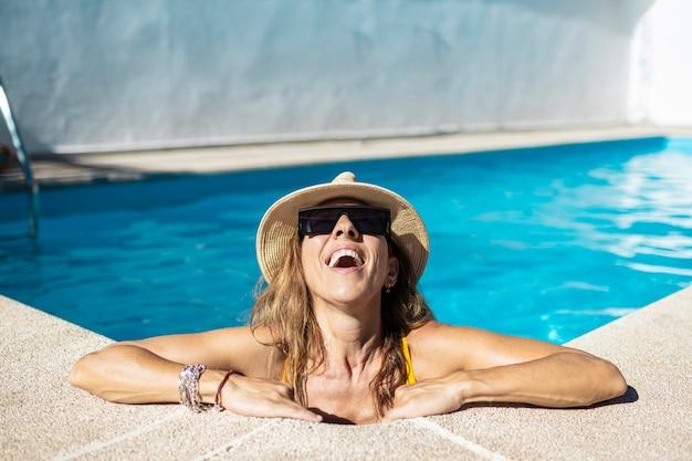 Roześmiana kobieta w basenie. opala się w basenie. ubrana jest w żółty strój kąpielowy i kapelusz.