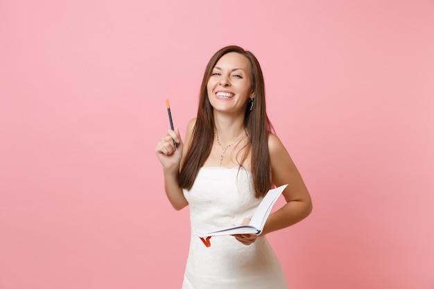 Roześmiana kobieta w białej sukni pisząca notatki w pamiętniku, zeszycie