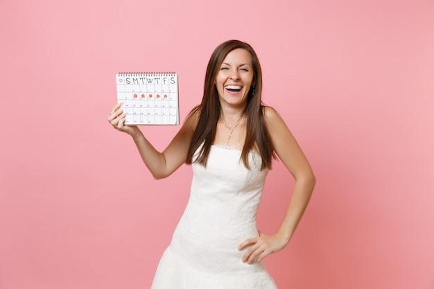 Roześmiana kobieta w białej sukni trzymająca kalendarz kobiecych okresów do sprawdzania dni menstruacyjnych
