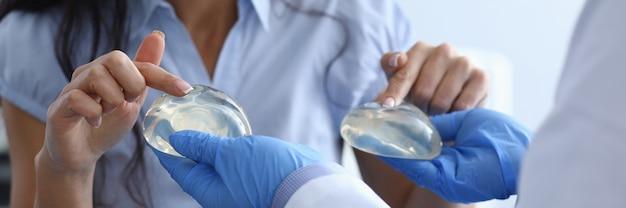 Roześmiana kobieta wybiera od lekarza implanty piersi