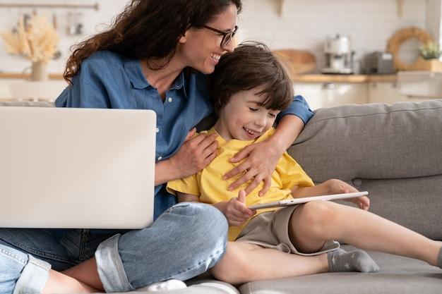 Roześmiana mama i dziecko z cyfrowym tabletem w roześmianych objęciach siedzą na kanapie w domu z laptopem na kolanach