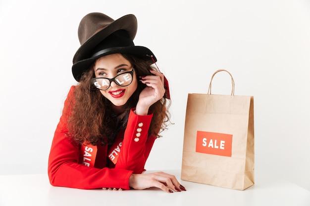 Roześmiana młoda caucasian dama blisko torba na zakupy