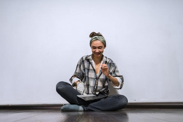 Roześmiana młoda dziewczyna w koszuli siedzi na podłodze i trzyma szpatułkę