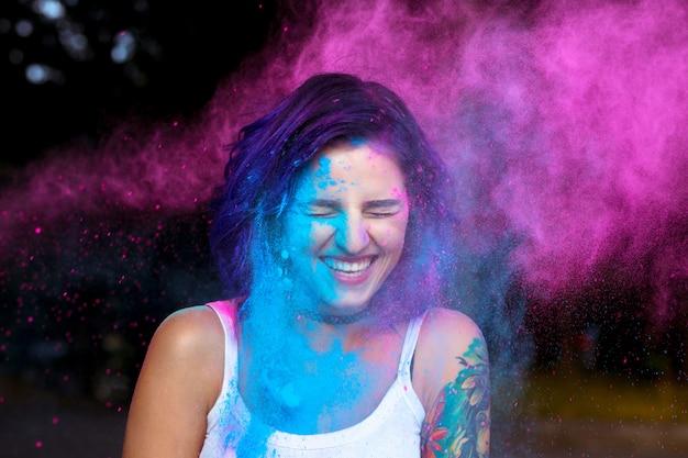 Roześmiana młoda kobieta z suchym, kolorowym proszkiem holi eksplodującym wokół niej
