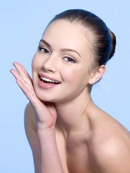 Roześmiana młoda piękna dziewczyna z ręką na twarzy na niebiesko