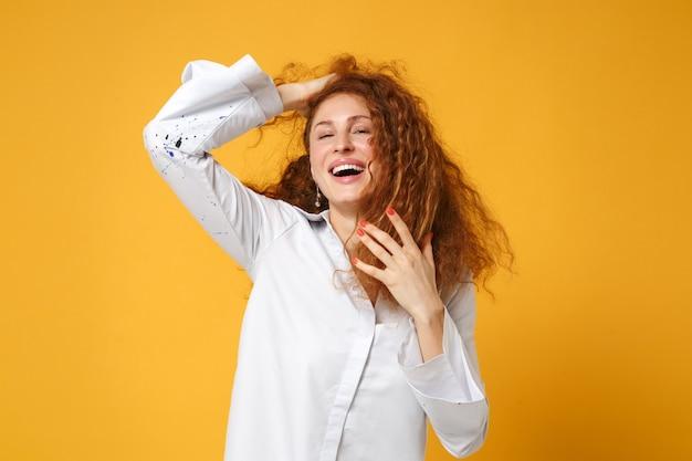 Roześmiana młoda ruda kobieta dziewczyna w białej koszuli pozuje odizolowana na żółto pomarańczowej ścianie