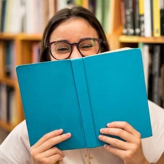Roześmiana nastoletnia uczennica chuje twarz za książką