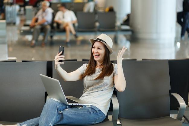 Roześmiana podróżniczka turystyczna kobieta pracuje na laptopie, robi selfie na telefonie komórkowym, rozkłada ręce, czeka w holu na lotnisku
