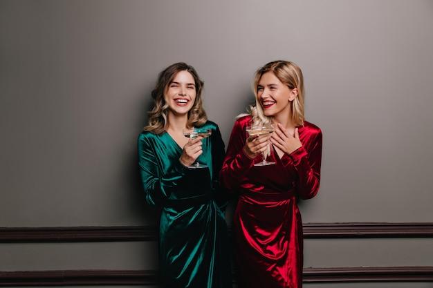 Roześmiana romantyczna kobieta w zielonym stroju pije wino. debonair europejki bawią się na imprezie.