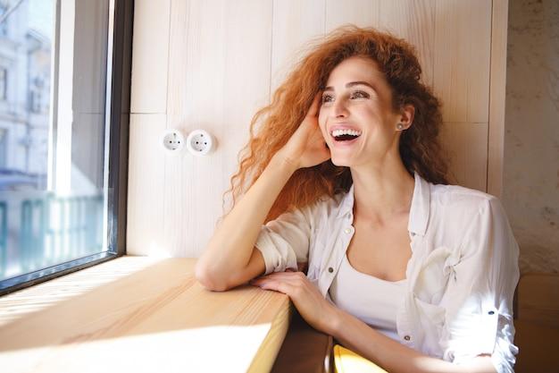 Roześmiana rudzielec młoda dama siedzi w kawiarni.