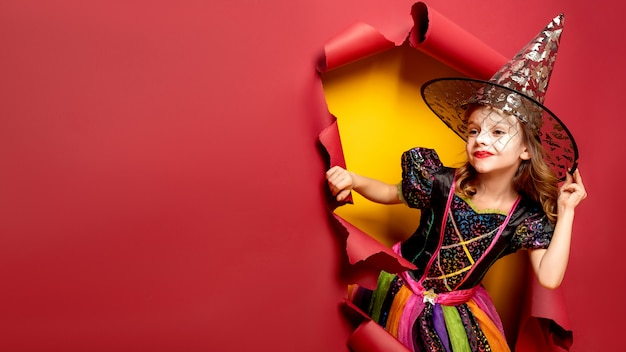 Roześmiana śmieszna dziecko dziewczyna w czarownica kostiumu w halloween