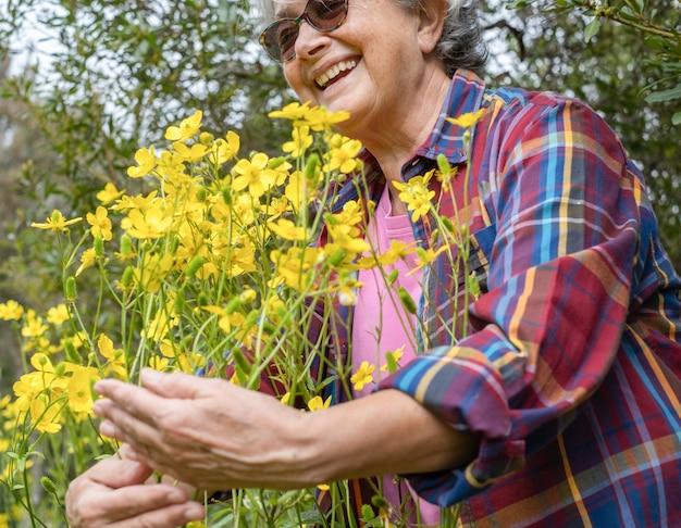 Roześmiana starsza kobieta przytula grupę żółtych kwiatów w pełnym rozkwicie w lesie.