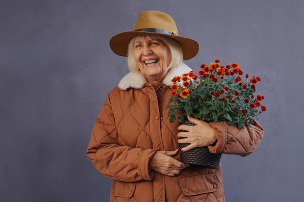 Roześmiana starsza kobieta w odzieży wierzchniej niosąca garnek z kwitnącymi kwiatami