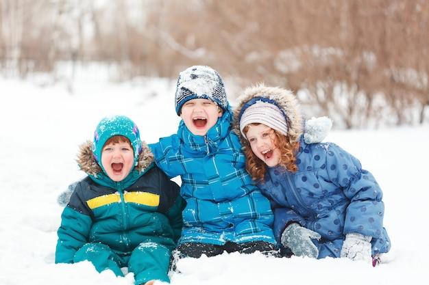Roześmiane dzieci siedzą na śniegu.