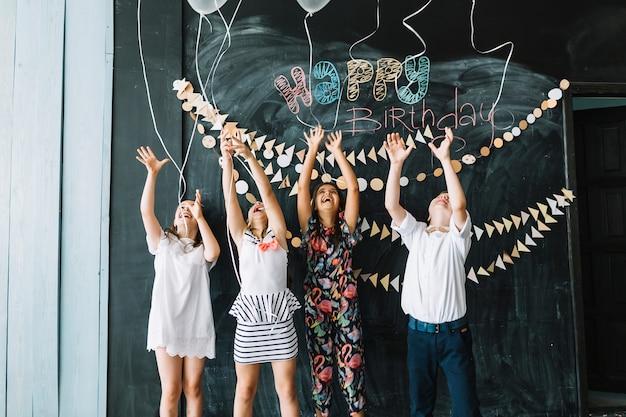 Roześmiane dzieci wypuszczające balony