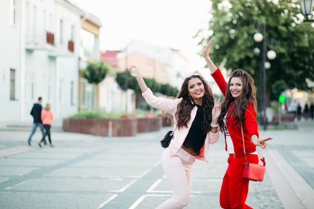 Roześmiane kobiety w eleganckich sportowych garniturach i torebkach na ulicy.
