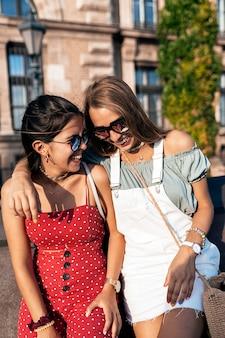 Roześmiane młode kobiety w letnim stroju i okularach przeciwsłonecznych spędzające razem czas podczas spaceru po moście