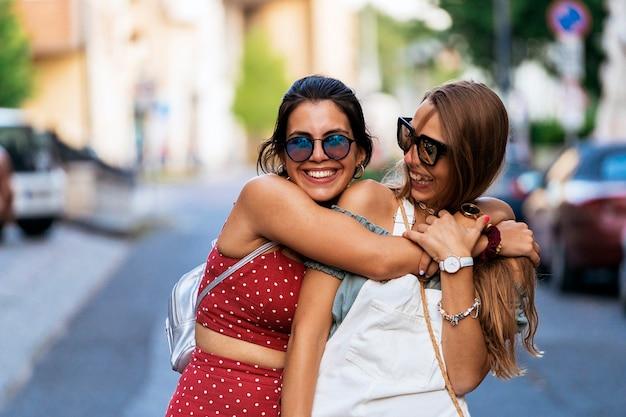 Roześmiane młode kobiety w letnim stroju i okularach przeciwsłonecznych spędzające razem czas podczas spaceru ulicą