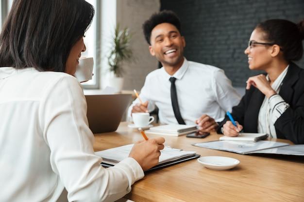 Roześmiani młodzi koledzy w pomieszczeniu coworking. skoncentruj się na kobiecie piszącej notatki.
