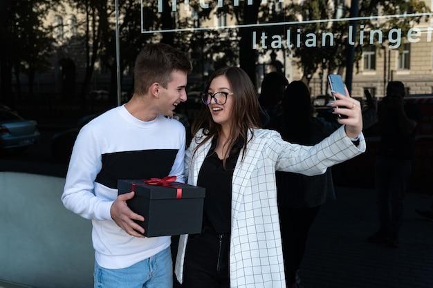 Roześmiani młodzi ludzie robią sobie selfie. facet z prezentem w rękach dla ukochanej. szczęśliwa para w dniu.